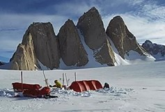 A man using snow kites to travel in the snow in the Antarctica mountains