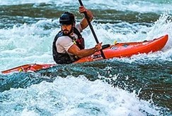 A man kayaking down the river of the Grand Canyon