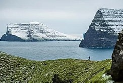 A runner running along the rugged and exposed trails of Faroe Islands